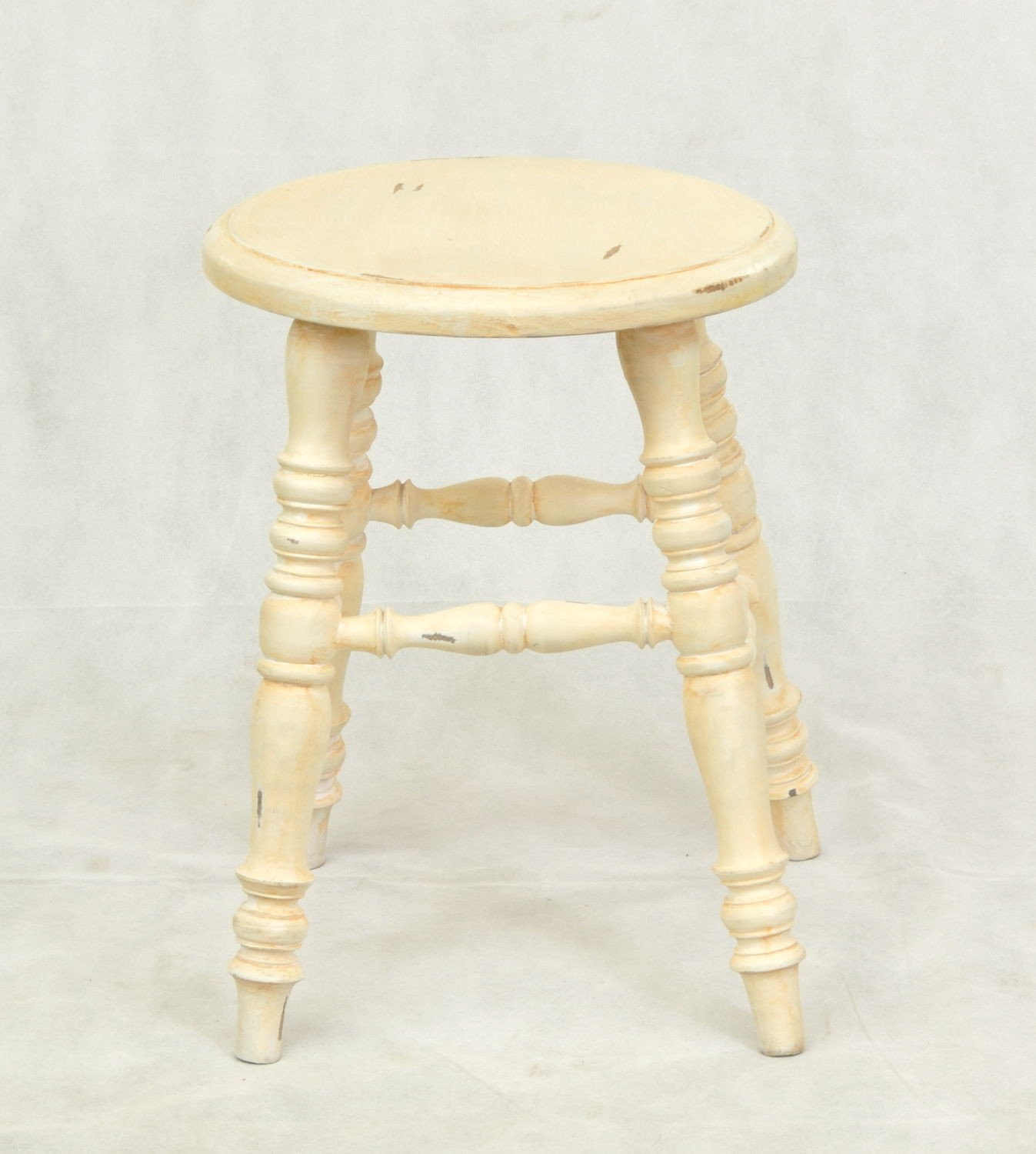 small round wooden stool with a distressed painted finish