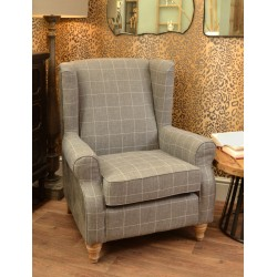 Tall wing back chair with grey tweed pattern fabric seat and grey faux leather back on a solid wood frame