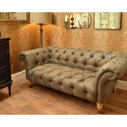 Faux leather small chesterfield sofa with tufted seat and back finished with dark wood turned front legs with castors