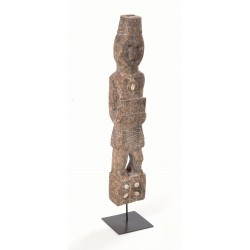 Dsitressed wooden tribal statue on a black metal stand with carved decoration and conch shell accessories